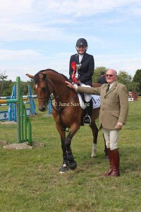Winner 1.20m Open - Amy Thomson riding Sunshine V receiving the Orles Barn Trophy presented by sponsor John Ewens of Spar in Ledbury